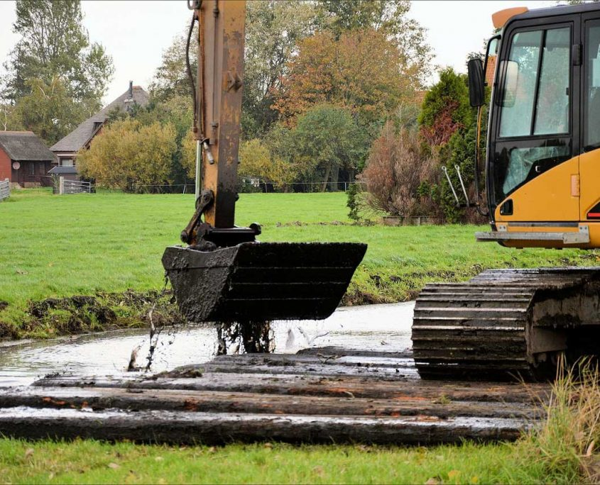 Image of an excavator ditch cleaning - Digger hire and excavator hire in Berkshire, Hampshire and Surrey - Ditching, drainage and flood minimisation - Berkshire, Hampshire and Surrey.