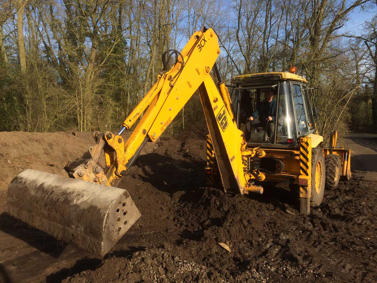 Image of a JCB at Holme Grange School in Wokingham Berkshire. Let The Digger Do It carrying out earthworks and drainage for a new staff car park at Holme Grange School Wokingham.